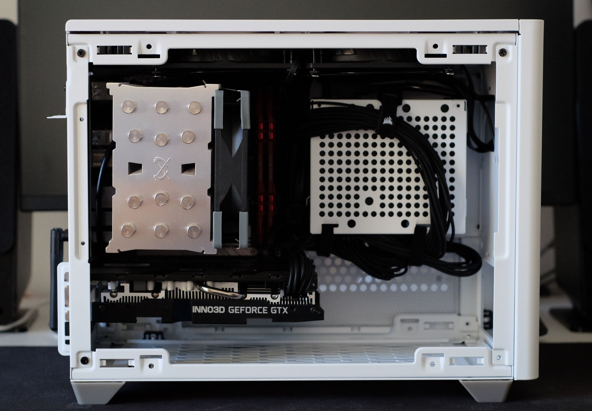 An open white computer case (CoolerMaster NR200), which shows a big CPU cooler, and a graphics card from Inno3D